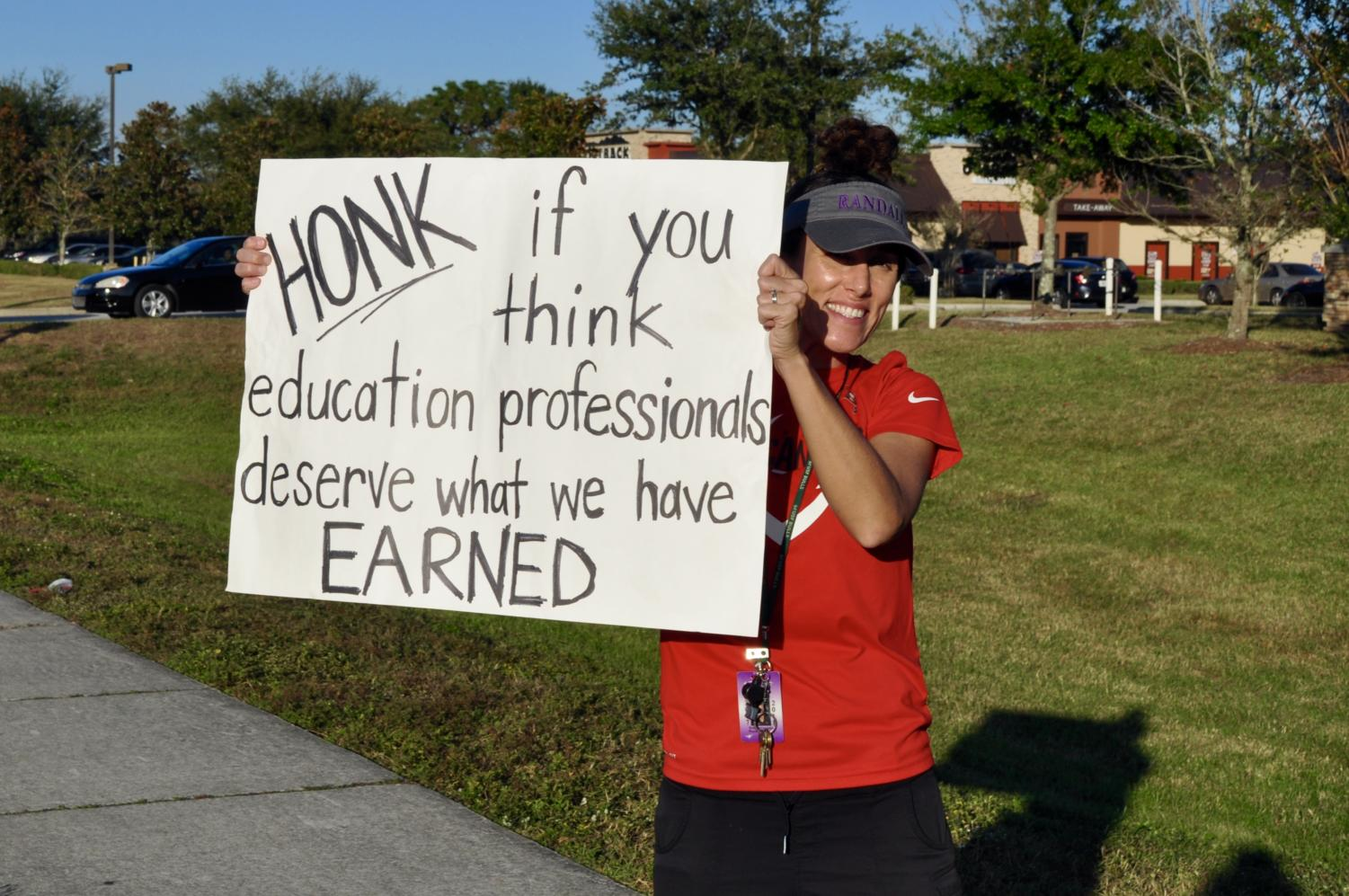 Teacher protests budget cuts that revoke promised pay raises outside Randall Middle School.